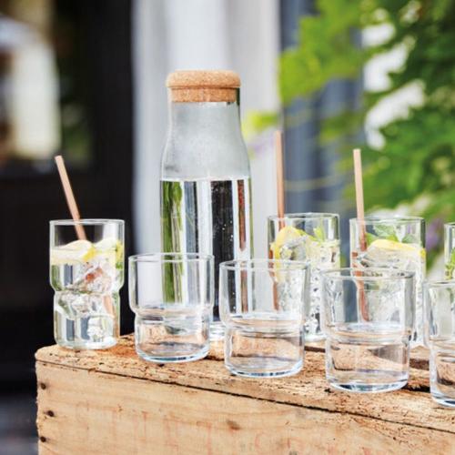 Glaskaraffe zwischen Gläsern